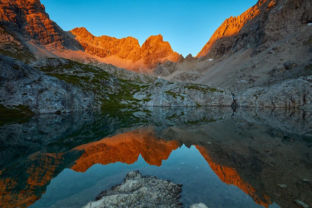 Bergsee in den Alpen mit Alpenglühen